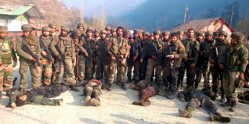 Uri: Army personnel stand near the dead bodies of militants who attacked Mohura army camp, in Uri on Saturday. PTI Photo(PTI12_6_2014_000052B)